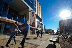 On a sunny December day, pedestrians walk past the University Square complex and Student Services Tower at 333 East Campus Mall.