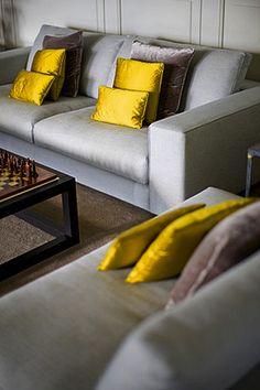 Effen sierkussens in geel en taupe combineren mooi op een lichtgrijze bank voor een krachtig kleuraccent