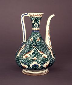 Ewer (pyriform). Curved spout, panels of scale ornament divided by split palmettes, cable band at rim and collar at neck. Made of black, red (bole), turquoise, cobalt painted and glazed ceramic, pottery.