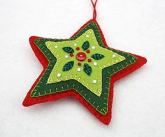 Red and green felt star Christmas ornament. Handmade felt hanging star with embroidered leaves and berries in greens and red, and a red button. A perfect gift or decoration . 4.25 inches / 11cm high,