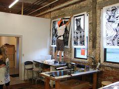 Ian hanging woodcuts on the wall.