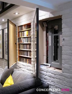 Hidden fuse box and media storage in wall hidden by hinged art frames for basement remodel by Concepts M2.