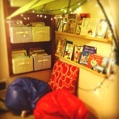 Kid book nook: books in bins on shelves. Cycle them out on the display shelves for easy access, fresh reading material, and easy cleanup.