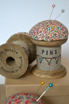 Pin cushion on a wooden spool - decorated with embroidery.