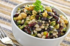 Recipe including course(s): Entrée; and ingredients: beans, black pepper, chili powder, fresh cilantro, frozen corn, garlic, green bell pepper, ground cumin, hot pepper sauce, kidney beans, lemon juice, lime juice, olive oil, red bell pepper, red onion, red wine vinegar, salt, sugar