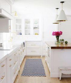 modern farmhouse white kitchen. White kitchen. Thick countertops. Simple cabinets. Brass pulls.