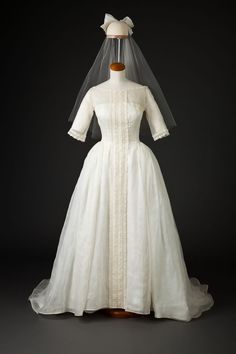 "Wedding Dress and Veil: 1962, cotton voile, imported Venetian lace, buttons. ""The bride, Barbara Taylor, was intrigued by a newspaper ad featuring the dress. Convinced it was ""the one,"" she purchased it at Harold, a women's specialty store in downtown Minneapolis. Barbara's wedding took place in Rhinelander, a small town in northeastern Wisconsin, in June 1962. She carried a small cascading bouquet of tiny yellow roses, white daisies, and trailing English ivy."""