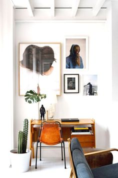 Gallery wall in office with palm plant