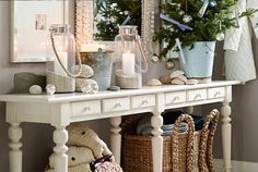 Make a coastal vignette with lanterns and sand.