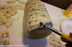 Paintbrush with decoupage gluing on torn sheet music to mason jar. gifts Easy DIY Sheet Music Mason Jar Vases - Girl, Just DIY! Mason Jar Vases, Mason Jar Lighting, Mason Jar Diy, Mason Jar Projects, Mason Jar Crafts, Music Centerpieces, Bottle Centerpieces, Sheet Music Crafts, Sheet Music Decor