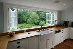 So Want This! Massive bifold windows are featured above an apron sink. Perfect for enjoying a crisp breeze.