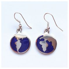 These delicate handcast alpaca silver and inlaid blue resin earrings depict the Western and Eastern hemispheres of the world. They are handmade by Fair Trade group Artesanas Campesinas, a women-owned