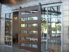 This 7' wide by 10' tall custom made wood barn door is in this atrium lobby of our current office project. We used the classic Rustica Hardware Industrial line heavy duty mount.
