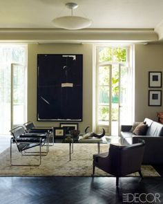 In the living room of Daniel Beauchemin and Marc de Laat's home in the Netherlands, vintage Wassily chairs by Marcel Breuer and a chair by Mosaic surround a cocktail table by Mies van der Rohe; the Ralph Rucci painting was a gift from the designer, and the rug is by Madeline Weinrib.