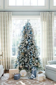 Flocked Christmas tree with blue glass ornaments and blue ribbon and presents below it.