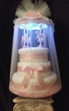 IV-Tier patent pending Dream Baby Light-Up Carousel Diaper Cake on a spinning base. By Colette & Brittany of A Unique Designer Gift Basket. Cake is sold at Newport Colony Baby 127 Newport Center Drive Newport Beach, CA. 92660 (949) 706 - 0633