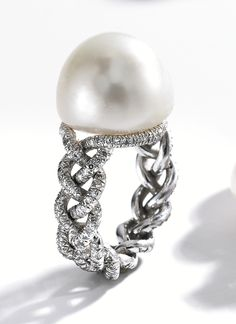 PLATINUM, NATURAL PEARL AND DIAMOND RING, JAR, PARIS The button-shaped natural pearl measuring approximately 13.9 by 13.9 by 11.2 mm, completed by a braided shank set with numerous single-cut diamonds, size 2¼, signed JAR Paris. With signed box.