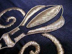 Satin Stitching with Metal Threads: Fleur-de-lis in silver thread on blue silk ground