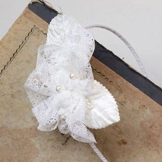 White lace headband with handmade floral applique. I have created these white flowers from a vintage lace, found in a tiny antique shop in Belgium. Flower centers are adorned with Swarovski 6mm pearls. There are also vintage velvet leaves, plus flower stamen. The floral applique sits on a satin covered headband (3mm wide) or a vintage lace (you tie it in the back).  The bride wear blush pink version of the headpiece.  Lovely hair accessory for a wedding or a communion. Great for pairing…