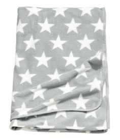 Light gray/stars. Throw in soft fleece with a printed pattern. Tape trim.