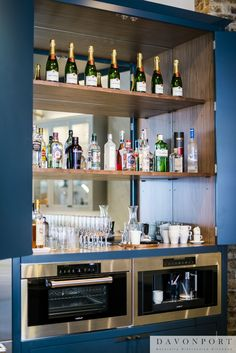 This 'gin bar' takes the traditional pantry and gives it a modern twist. Set above a Miele coffee machine and steam oven the mirrored back wall and walnut shelves are used to display gin and champagne.