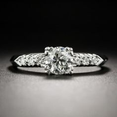 This straight ahead ultra-sparkler, hand fabricated in platinum, circa 1940s, features a beautiful, bright-white, high-quality, transitional round brilliant-cut diamond, weighing .62 carat. The scintillating stone is modestly embellished on each side with a slender row of small single-cut diamonds leading to a sleek knife-edge ring shank. Traditional, tailored and timeless. Currently ring size 6 1/4.