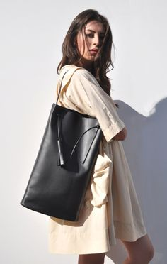 Anaise, BUILDING BLOCK TALL BAG Minimalist smooth black leather bag with single rubber shoulder strap and leather tassel. Apart from leather lined base, inner compartment is unlined. Handcrafted in LA.  #anaise #bag