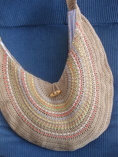 sling tote or beach bag.  free pattern.  love the bright color embroidery on top of neutral yarn.