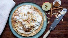 Apfel-Haferflocken-Kuchen, ein halber Apfel, Zimtstangen und Mandeln liegen auf einem Tisch.
