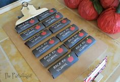 These are candy bar wrappers.  They would be easy to do out of black construction paper, an apple sticker and writing with chalk or a white paint marker.