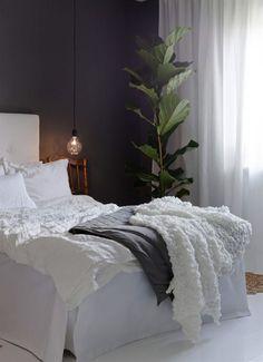 Den gröna växten i ena hörnet blir en färgklick mot de grå väggarna. Den gamla stolen har Saras gammalmorfar byggt i början av 1900-talet. Sängkläder från Ikea, örngott och matta från H&M home. Grått överkast från Ellos. På varsin sida av sängen hänger lampsladdar och glödlampor från Clas Ohlson.