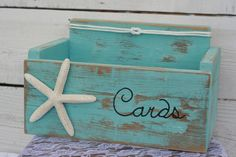 This is a Robins Romantic Original Design and is made from reclaimed wood~ handmade wood box to hold wedding, anniversary or baby shower cards! This card box has a nautical beach ocean theme with pretty aqua blue distressed paint.  Color shown is # 4 Aqua This card box will hold approximately 100 to 125 cards. If you need a larger box just contact me.  Purchase the item as pictured or choose the color you would like from our color palette listed above (select color). Note: All boxes will be…