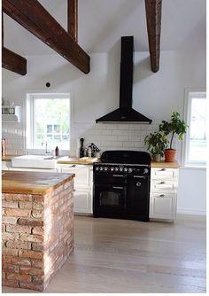 Svarta vitvaror och en murad köksö.