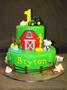 John Deere first birthday cake - This John Deere cake was for a little boy turning one.  They wanted the John Deere theme incorporated with farm animals.  Everything is made out of gumpaste and fondant except for the tractors.
