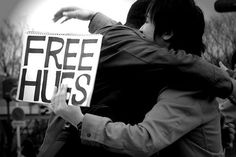 Caught in the act! Somebody promoting free hugs as an act of kindness to the public is snapped in a picture mid-hug
