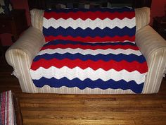 """My husband wanted a Fourth of July crochet piece to cover our hand-me-down love seat that was torn and stained. We originally considered trying the Never-Ending Granny Square pattern from Michael Sellick, but my husband didn't like the effect. So I thought, """"what would I like to learn next?"""" and suggested, how about a ripple afghan. He loved the idea, with the caveat that I use bright white, bright red and bright blue yarns."""