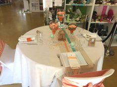 Voici une table aux allures vintages, composé d'un dégradé d'orange, de saumon et de vert d'eau. Au centre de table, un chemin de table en lin est croisé avec un autre chemin en dentelle ivoire et de 2 bandes de rubans en satin, les perles de pluies oranges, les granulats blanc et les bougies vert d'eau viennent donner de la luminosité à la table. Nous jouons sur la hauteur avec des bougeoirs sur pied, remplis de granulats oranges et de gerberas saumon.
