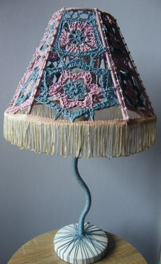 The lamp is unique and one of a kind. The lampshade is made of lacy hand-crocheted patterns, sewn to the frame. The colors, and forms carefully assorted to create an effect of vintage charm and Innocence, while the stand and base lend the product a more quirky and modern feel.  It would serve well in a nursery or a bedroom, but would also suit a living area or working space.     For more info or to buy, click the link below