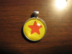 Circle glass pendant with red star on yellow background in a silver setting.