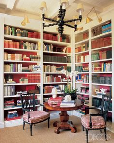 Elle Decor; Public-relations executive Mike Clifford brought drama to the library he created in the entry of his Hollywood Hills house by painting the walls backing the bookcases in a Farrow & Ball red.   Spool chandelier: Paul Merra  Photographer: Grey Crawford   Issue: November 2005