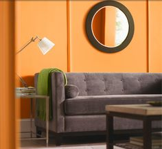 This room from the Home Depot Summer Style Guide makes me so happy... love the orange walls with the gray couch and that round mirror. LOVE.