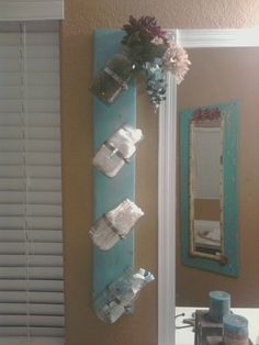 SAW THIS IDEA ONLY GOING HORIZONTAL BUT WANTED ONE VERTICAL TO FIT IN AN AREA, I PAINTED IT TEAL TO GO ALONG WITH MY BATHROOM COLORS AND USED HOSE TUBING TO KEEP THE MASON JARS ON TO THE BOARD AND ADD WHATEVER YOU LIKE: