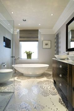 Mosaic floor tiles with a floral pattern create a beautiful feature in this modern bathroom #Deluxe
