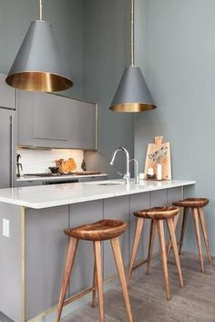 Grey pendant lighting with gold interior accents add an extra dimension to this tiny galley kitchen, and despite the lofty ceilings, make it feel considerably more cosy. - Interior Homes Gold Interior, Kitchen Interior, New Kitchen, Interior Design, Kitchen Ideas, Kitchen Grey, Brooklyn Kitchen, Apartment Kitchen, Gold Kitchen