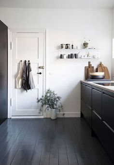 sleek black and white kitchen with painted black floors and cabinets…