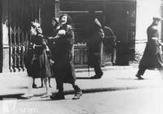 A destitute woman carrying a dead infant cries out as she walks along a street in the Warsaw ghetto