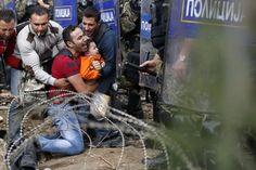 ヨーロッパ移民問題の現状 > ギリシャとマケドニアの国境近くで、マケドニアの警察機動隊に入国を懇願する子どもを抱いた男性。2015年8月21日、ギリシャ・イドメニ。
