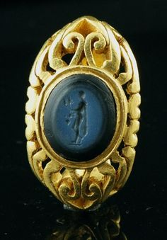 Gold Ring and intaglio nicolo. Rome, 3rd century. Gold ring end, massive, chiseled to ring flared and wide shoulders, worked in openwork. The oval bezel is set with an agate intaglio nicolo black and blue, engraved with a naked male figure, Length, facing left, a pendant cloak on his back and clutching the ears of corn and a bunch grape, probably the god Bonus Eventus. Roman work of the first half of the 3rd century.  The intaglio is perhaps earlier and reused on a 3rd century frame.