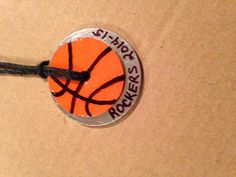 "Basketball necklace version 2: 1"" washer, orange scrapbook paper, ModPodge, sharpies and ModPodge Dimensional Magic.  Used a 1 1/2"" washer under it with some black hemp."