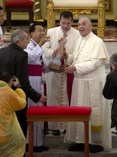 Pope Francis, right, looks at the Palo Cathedral, as he arrives for a short address, Saturday, Jan. 17, 2015. Francis traveled to the far eastern Philippines to comfort survivors of devastating Typhoon Haiyan in 2013 on Saturday, but cut his own trip short because of another approaching storm. (AP Photo/Alessandra Tarantino)